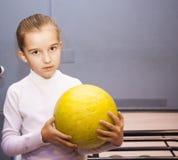 Kleines Mädchen steht und hält den Ball im Bowlingspielverein Lizenzfreie Stockfotos