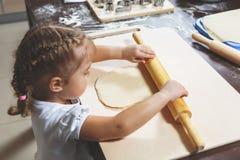 Kleines Mädchen stellt den Teig mit einem großen Nudelholz für die Herstellung von selbst gemachten Plätzchen bereit stockfoto