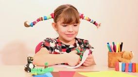 Kleines Mädchen stellt Papierschnurrbart her stock video footage