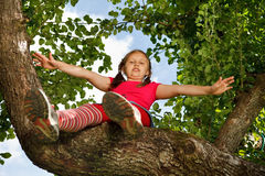 Kleines Mädchen stieg auf Baum lizenzfreies stockfoto