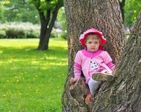 Kleines Mädchen stieg auf Baum und dem Sitzen auf ihm Lizenzfreies Stockfoto