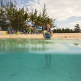 Kleines Mädchen am Strand, halb Unterwasseransicht Lizenzfreies Stockbild