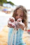 Kleines Mädchen streuen Sand Throw ihre Finger stockfotografie