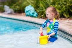 Kleines Mädchen am Swimmingpool Stockfoto