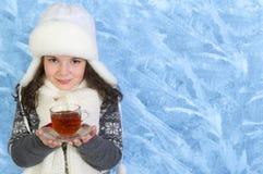 Kleines Mädchen trägt eine Tasse Tee auf Winterhintergrund Stockbilder