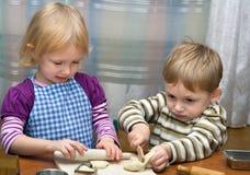 Kleines Mädchen und der Junge helfen auf Küche stockbilder