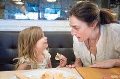 Kleines Mädchen und Frau, die Pizza und das Lächeln isst Lizenzfreie Stockbilder