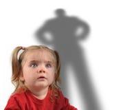 Kleines Mädchen und furchtsamer Schatten auf Weiß Stockbilder