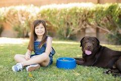 Kleines Mädchen und hübscher Hund, die im Park sitzt lizenzfreies stockbild