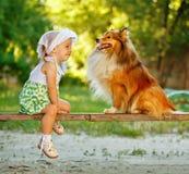 Kleines Mädchen und Hund, die auf einer Bank sitzt Lizenzfreie Stockfotografie