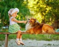 Kleines Mädchen und Hund, die auf einer Bank sitzt Stockbilder