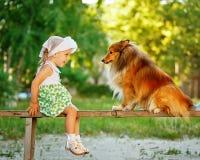 Kleines Mädchen und Hund, die auf einer Bank sitzt Lizenzfreie Stockfotos