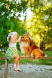 Kleines Mädchen und Hund, die auf einer Bank sitzt Lizenzfreie Stockbilder