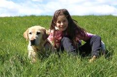 Kleines Mädchen und Hund, die auf grüner Wiese in den Bergen liegt Stockfoto