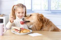 Kleines Mädchen und Hund, die zusammen zu Mittag isst Lizenzfreie Stockbilder