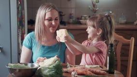 Kleines Mädchen und ihr beißender Käse der Mutter mit Löchern stock video