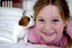 Kleines Mädchen und ihr netter Welpe auf einem weißen Bett lizenzfreies stockbild