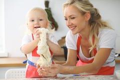 Kleines Mädchen und ihre blonde Mutter in den roten spielenden und beim Kneten des Teigs in der Küche lachenden Schutzblechen Hom Lizenzfreie Stockfotografie