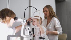 Kleines Mädchen und ihre Mama in der Augenheilkunde - Optometriker, der kleines Kind-` s Vision überprüft stockbilder