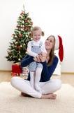 Kleines Mädchen und ihre Mamma, die Spaß am Weihnachten hat Stockfotografie