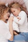 Kleines Mädchen und ihre Mutter, die auf einem Bett liegt Stockfotografie