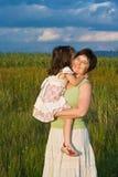 Kleines Mädchen und ihre Mutter, die draußen bleibt Lizenzfreies Stockfoto
