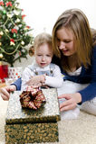 Kleines Mädchen und ihre Mutter entpackt das Geschenk Stockfotografie