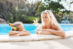 Kleines Mädchen und ihre Mutter mit Cocktail im tropischen Strandpool Lizenzfreie Stockbilder