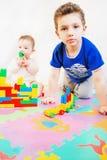 Kleines Mädchen und Junge bauen ein Haus aus Block heraus auf Lizenzfreie Stockbilder
