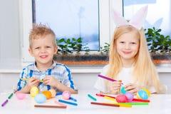Kleines Mädchen und Junge in den Kaninchenhäschenohren auf Kopf bereiten sich für Ostern und malende Eier vor Bunte Markierungen  lizenzfreie stockfotografie