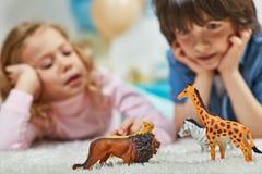 Kleines Mädchen und Junge, die mit Interesse Spielwaren betrachtet Lizenzfreie Stockfotografie