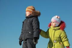 Kleines Mädchen und Junge, die am Schnee steht Stockfotos