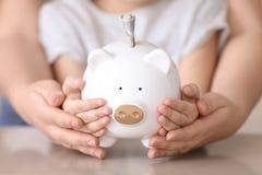 Kleines Mädchen und junge Frau, die Sparschwein hält Lizenzfreie Stockbilder