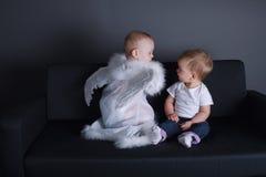 Kleines Mädchen und Junge im Engelskleid Stockfotografie