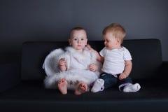 Kleines Mädchen und Junge im Engelskleid Lizenzfreies Stockbild