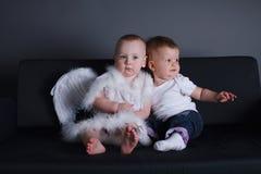 Kleines Mädchen und Junge im Engelskleid Stockfotos