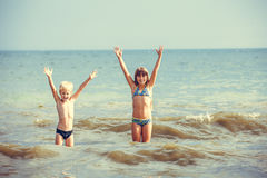 Kleines Mädchen und Junge im Meer Stockfotos