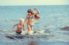 Kleines Mädchen und Junge im Meer Stockbilder