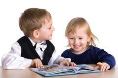 Kleines Mädchen und Junge lasen das Buch Stockfotografie