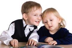 Kleines Mädchen und Junge lasen das Buch Stockbild