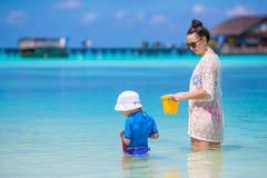 Kleines Mädchen und junge Mutter während des Strandes machen Urlaub Stockbilder