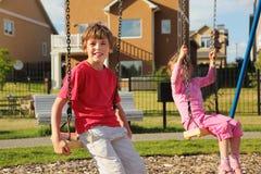 Kleines Mädchen und Junge sitzen auf Schwingen nahe Häuschen Lizenzfreie Stockfotos