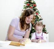 Kleines Mädchen und Mutter bereiten Plätzchen zu Lizenzfreies Stockbild