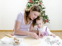 Kleines Mädchen und Mutter bereiten Plätzchen zu Lizenzfreies Stockfoto