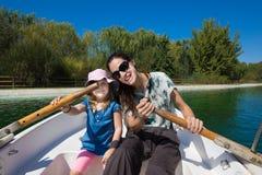 Kleines Mädchen und Mutter, die Rudersport in einem Boot aufwirft Lizenzfreies Stockfoto