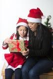 Kleines Mädchen und Mutter, die Weihnachten vorhanden küsst und gibt lizenzfreies stockbild