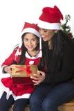 Kleines Mädchen und Mutter, die Weihnachten vorhanden küsst und gibt stockfotografie