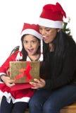Kleines Mädchen und Mutter, die Weihnachten vorhanden küsst und gibt lizenzfreies stockfoto