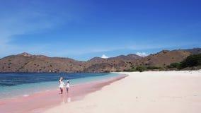 Kleines Mädchen und Mutter gehen auf rosa Strand stock video