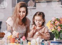 Kleines Mädchen und Mutter malt Eier Junges Küken in Wanne, 2 malte Eier und Blumen Stockbild